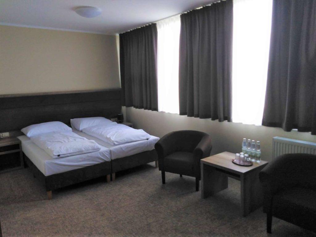 stolik i łóżko w pokoju dwuosobowym